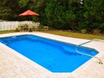 Grande fiberglass swimming pool in backyard