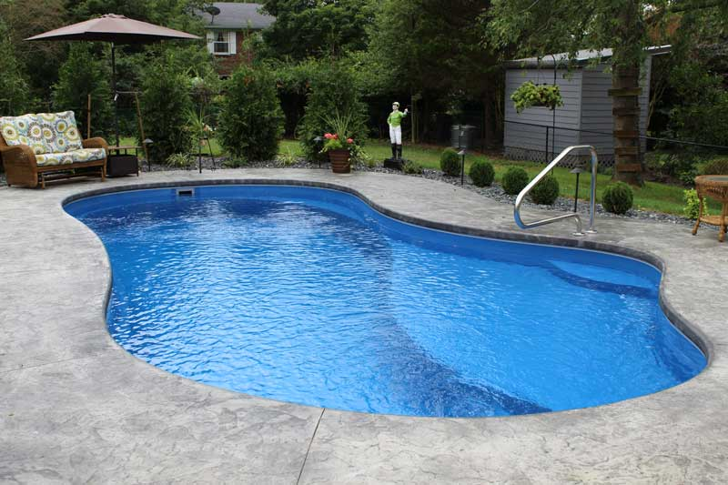 Inground Fiberglass swimming pool with Ocean blue water and landscaping