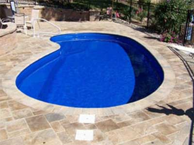The Opal pool filled with water and stone patio surrounding it