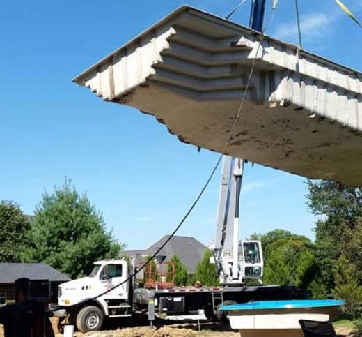 Truck with crane lowering pool into the ground