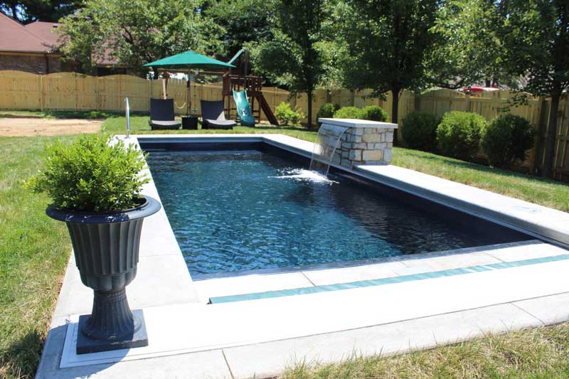The Vision design pool in backyard with water fountain and landscaping