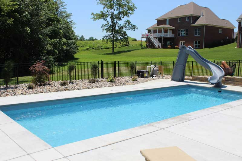 Fiberglass pool with slide and brickhouse in the background
