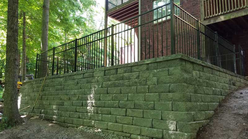 Stone Retaining Wall on the side of a Brick House in Wooded Area