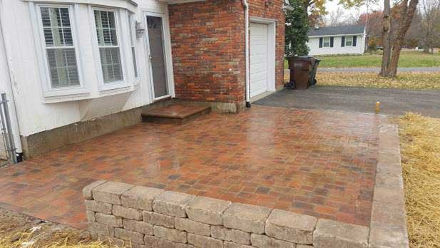 Fresh Wet Concrete Patio Paved with Red Bricks in Front of House
