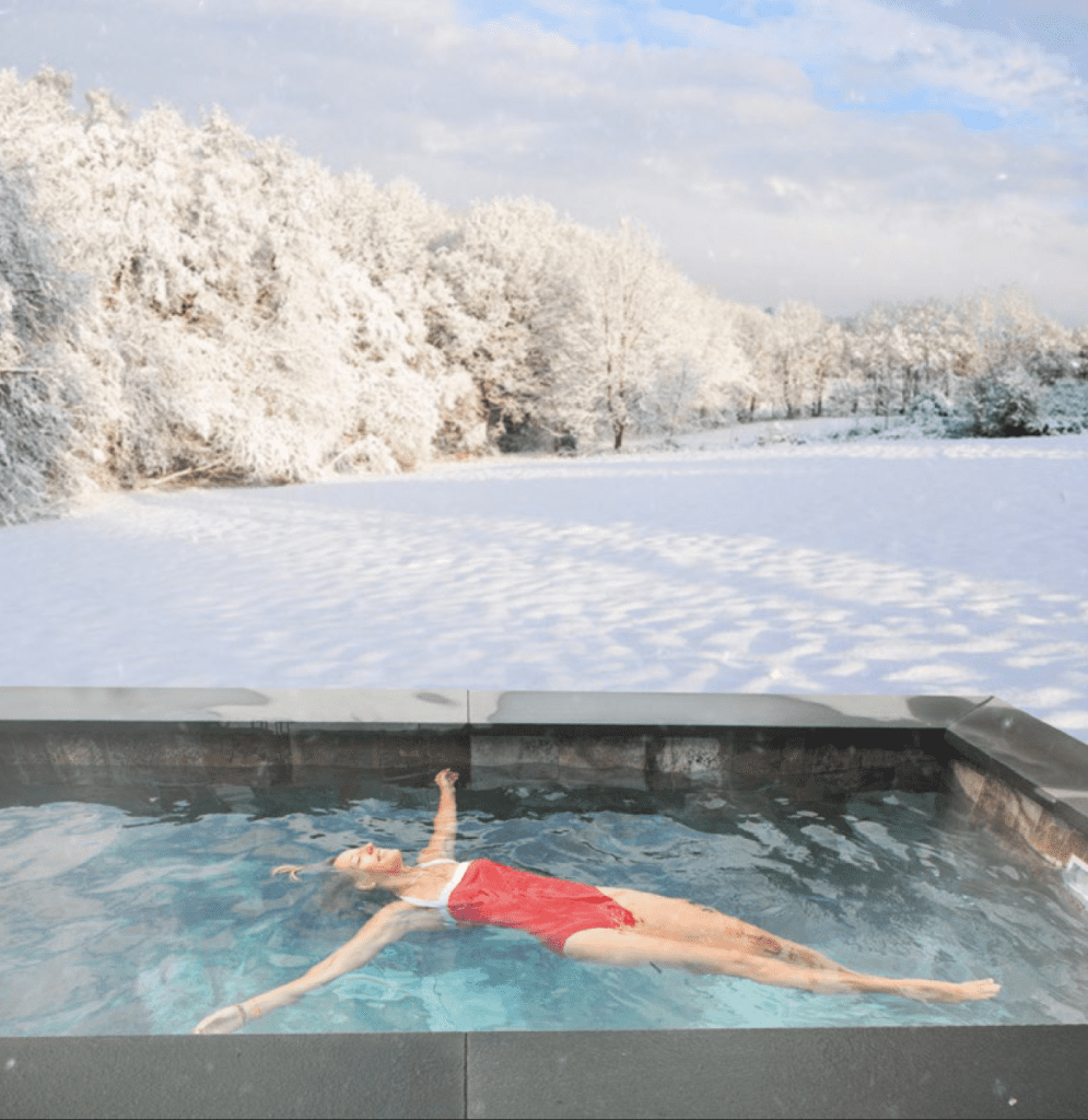 Woman floating in cocktail pool in the winter with snow on the ground