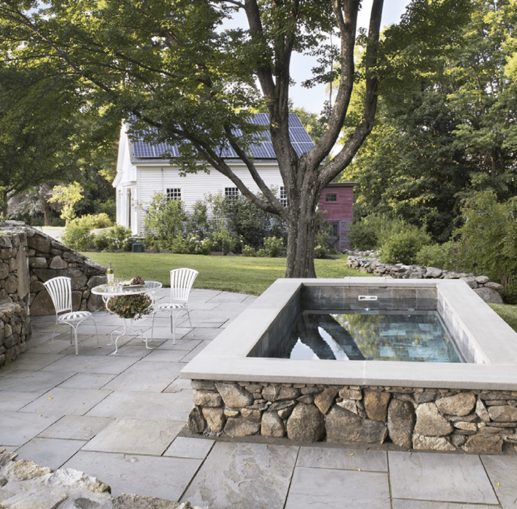 Cocktail Pool with stone patio behind white house